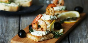 Appetizer canape with shrimp and olives on cutting board on tabl